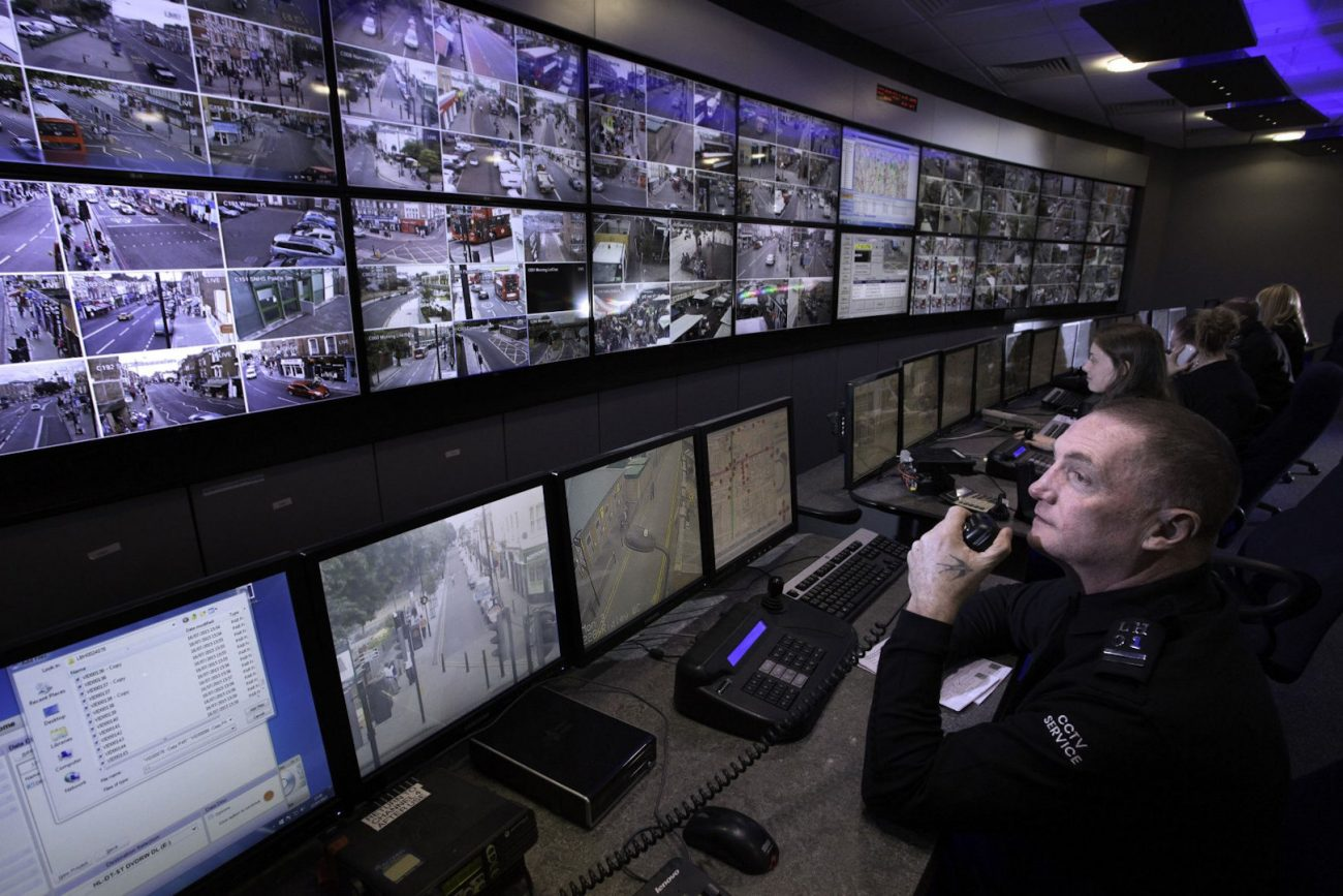 security guards using cctv software viewing network cameras on monitors