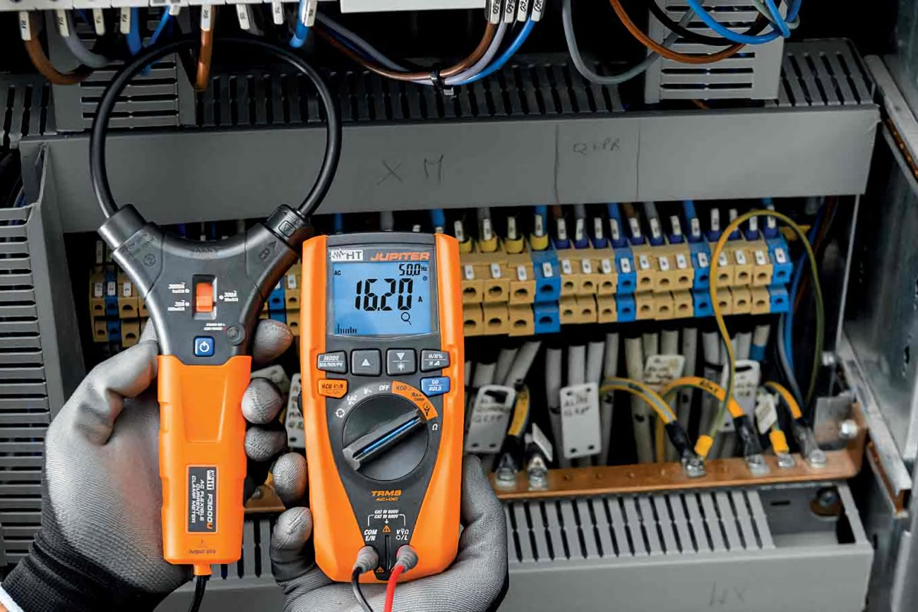 electrician measuring power on switchboard with power analyzer
