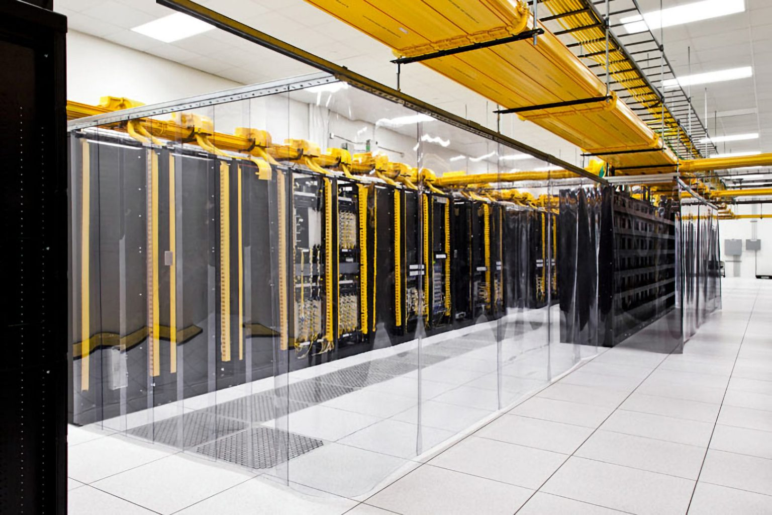 yellow structured fibre cabling to racks in large data centre