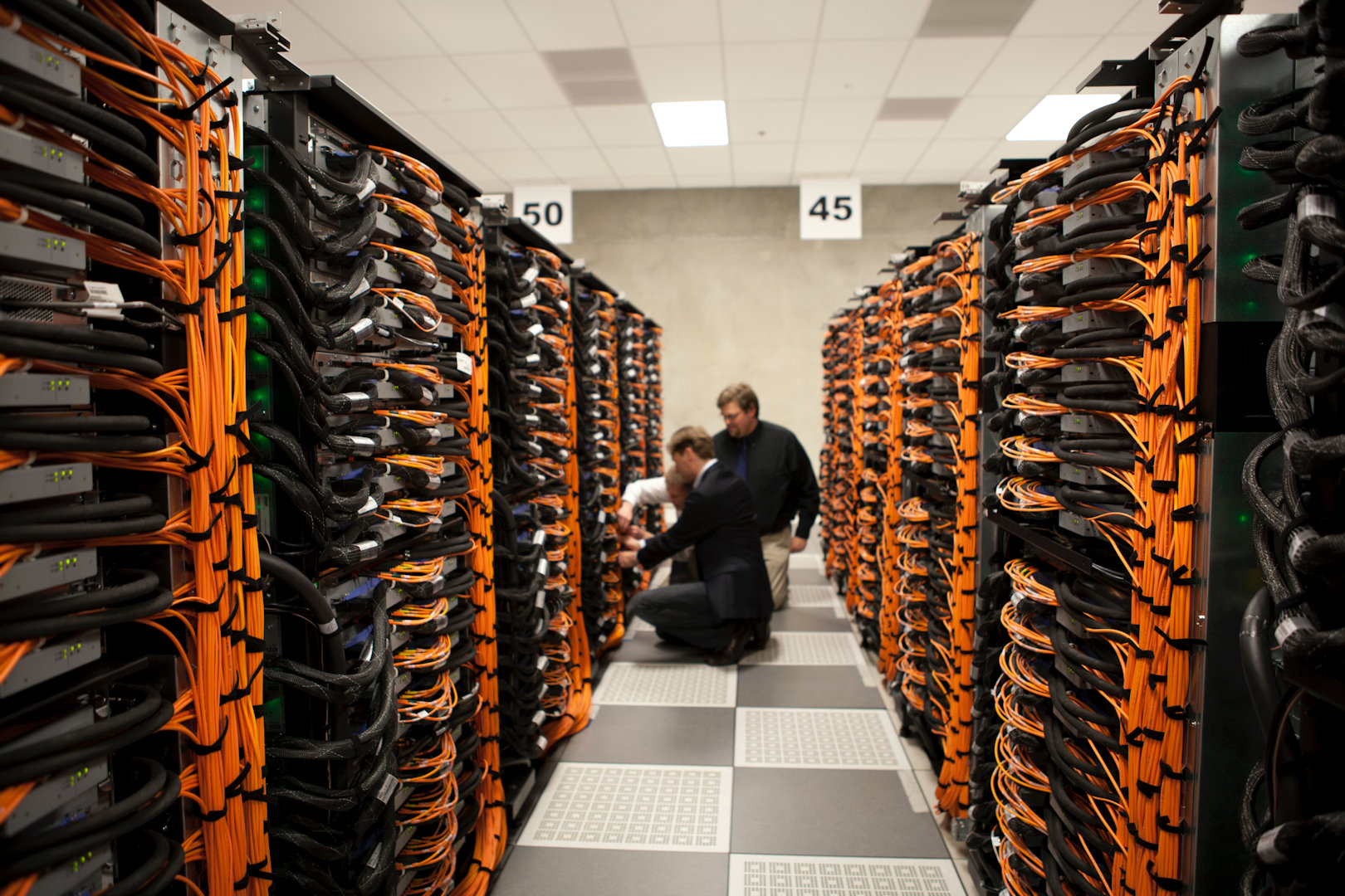 engineers working on structured data cables within data centre