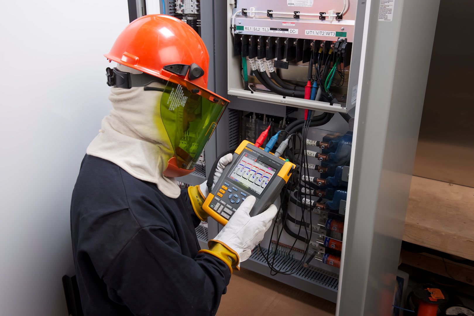 electrician using a power analyser on electrical switchboard