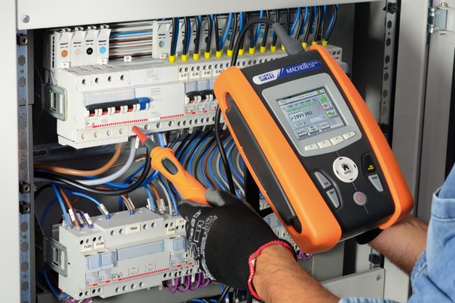 electrician working on switchboard power analysis