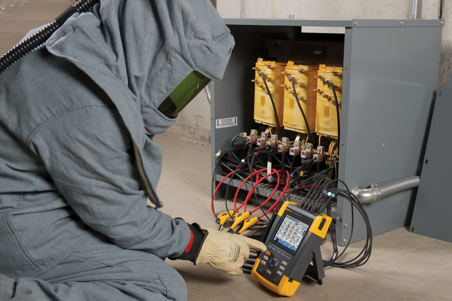 electrician wearing explosion suit measuring power on transformer