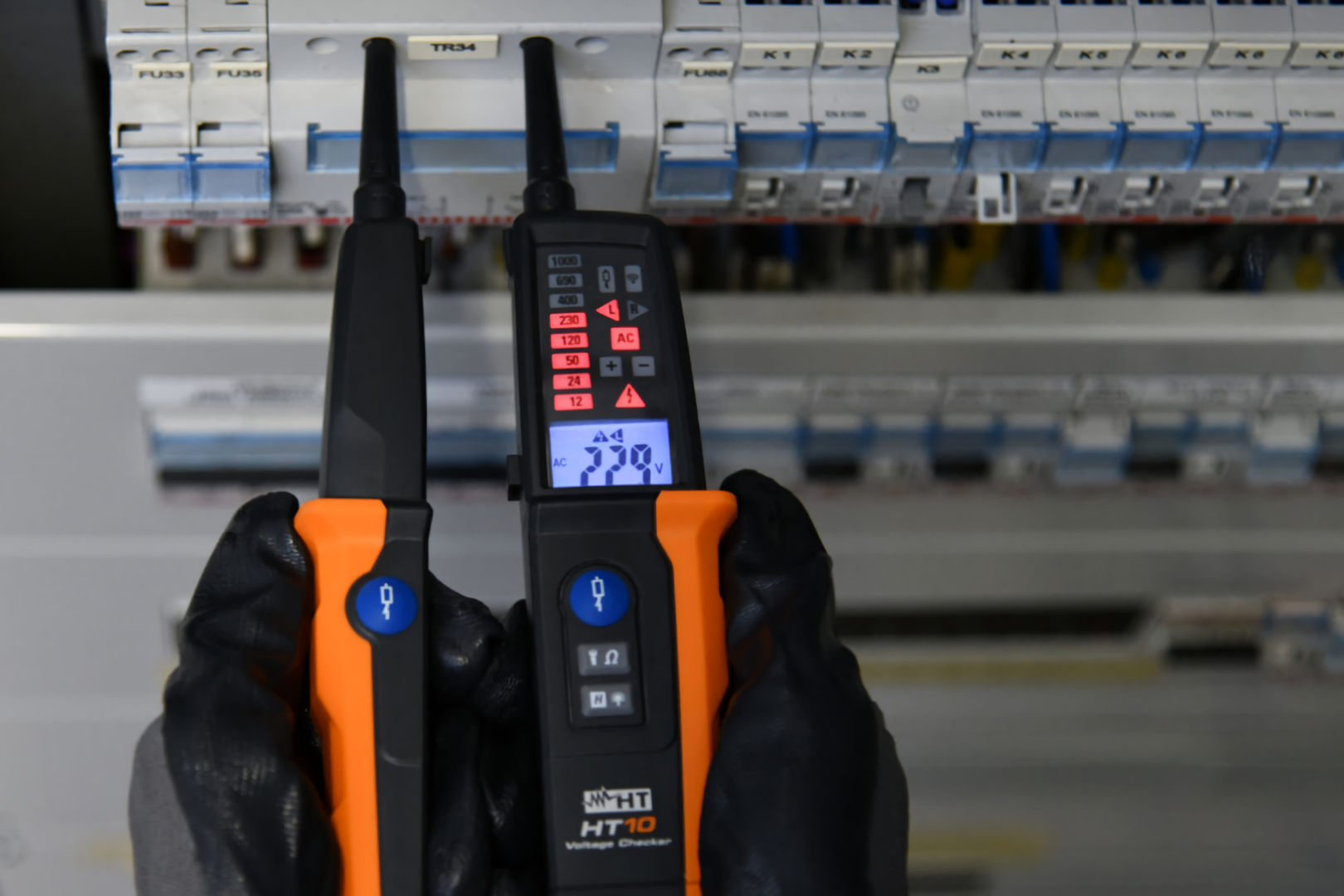 electrician measuring power on switchboard wearing ppe safety gloves