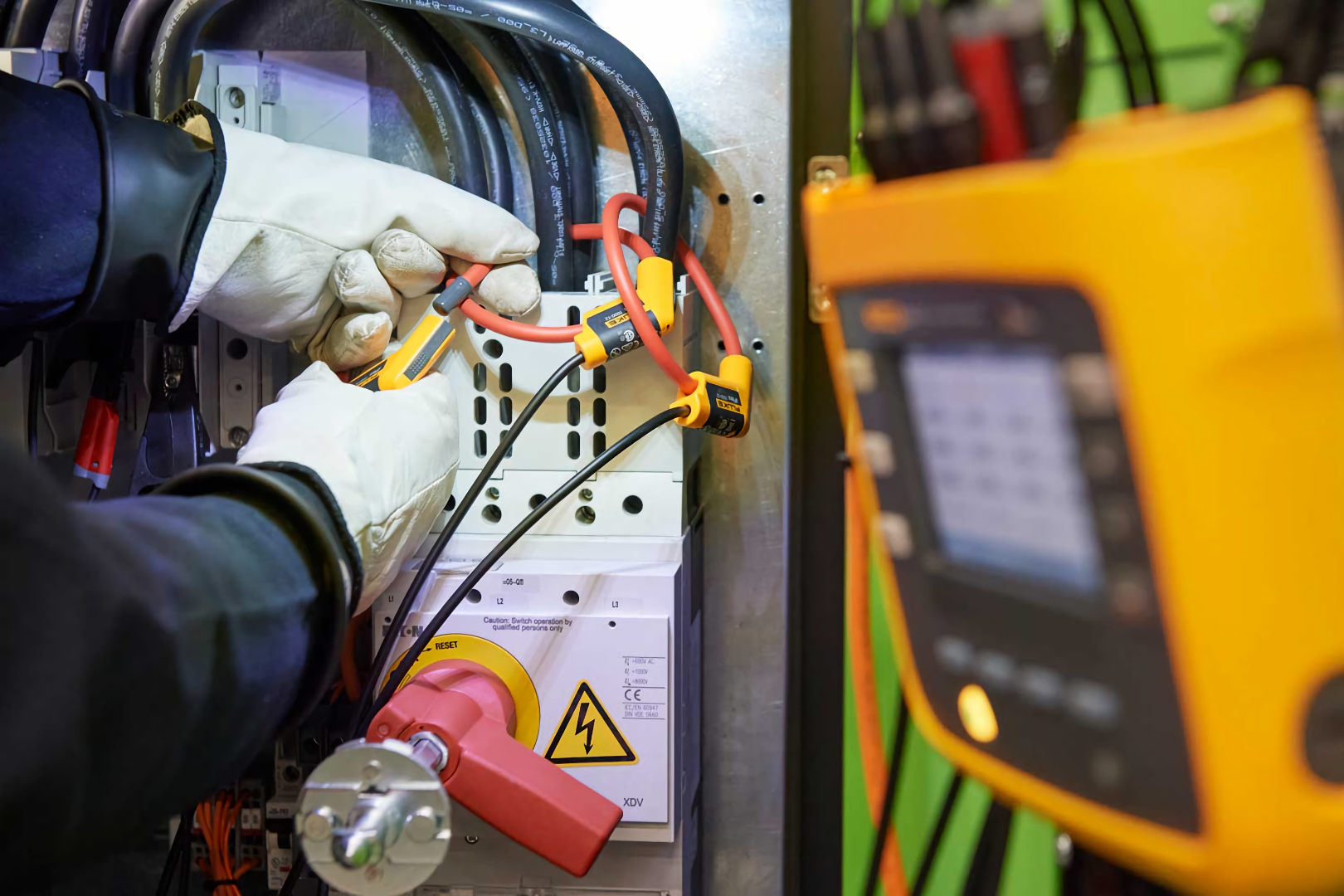 electrician using power analyzer on electrical switchboard