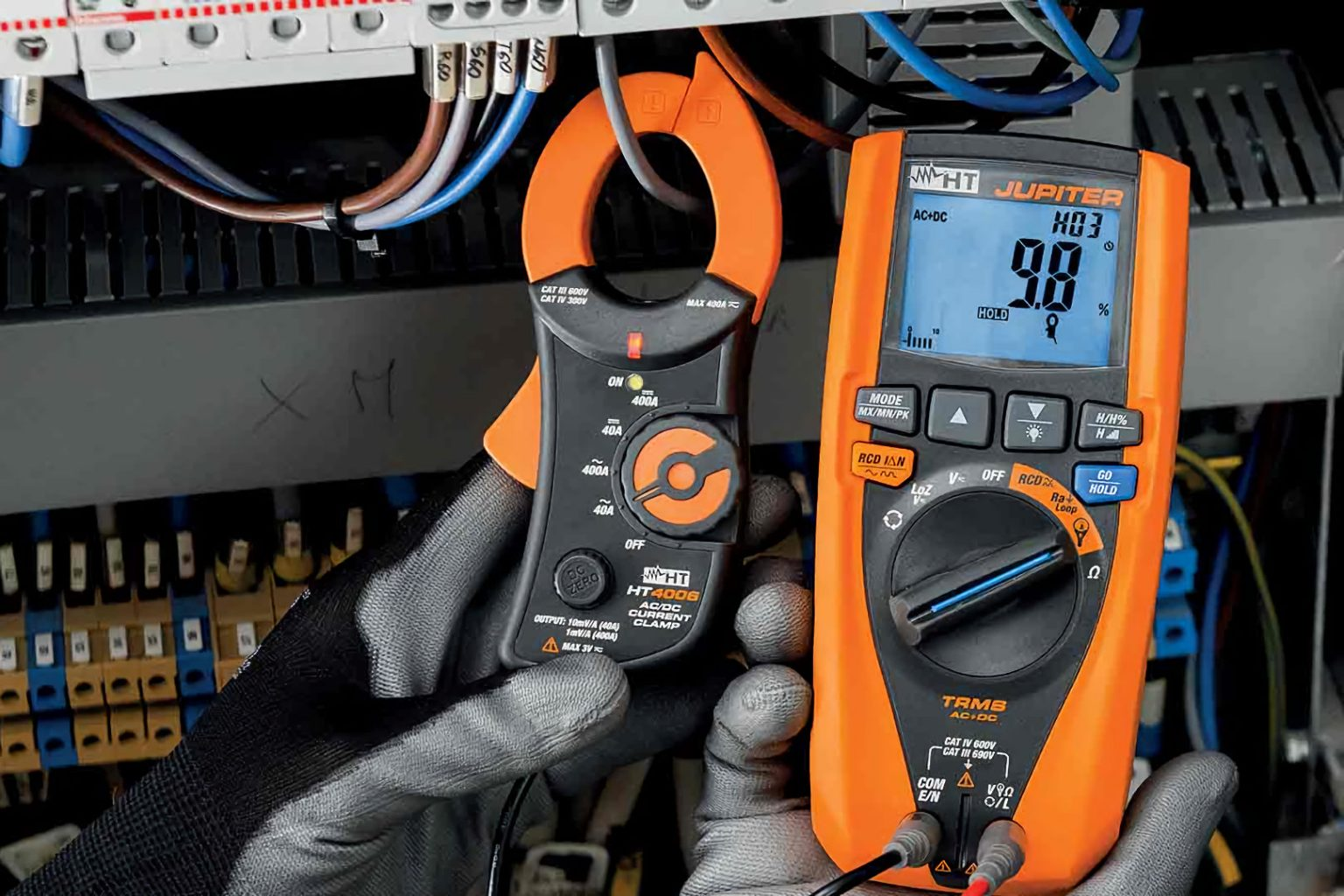electrician using power analyser on switchboard to measure amps