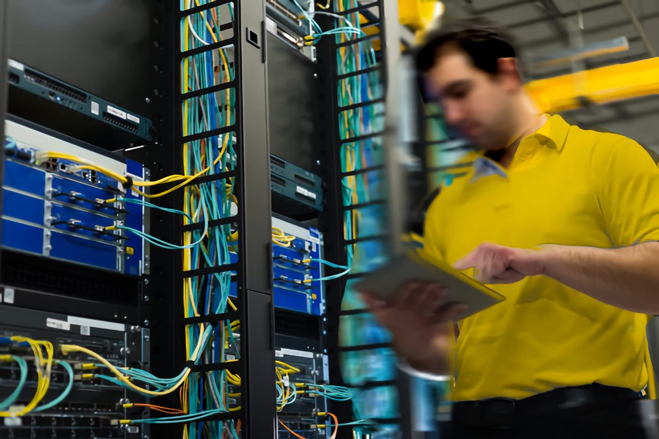 technician analysing network data cables in data centre