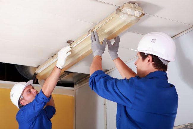 electricians replacing fluorescent light baton