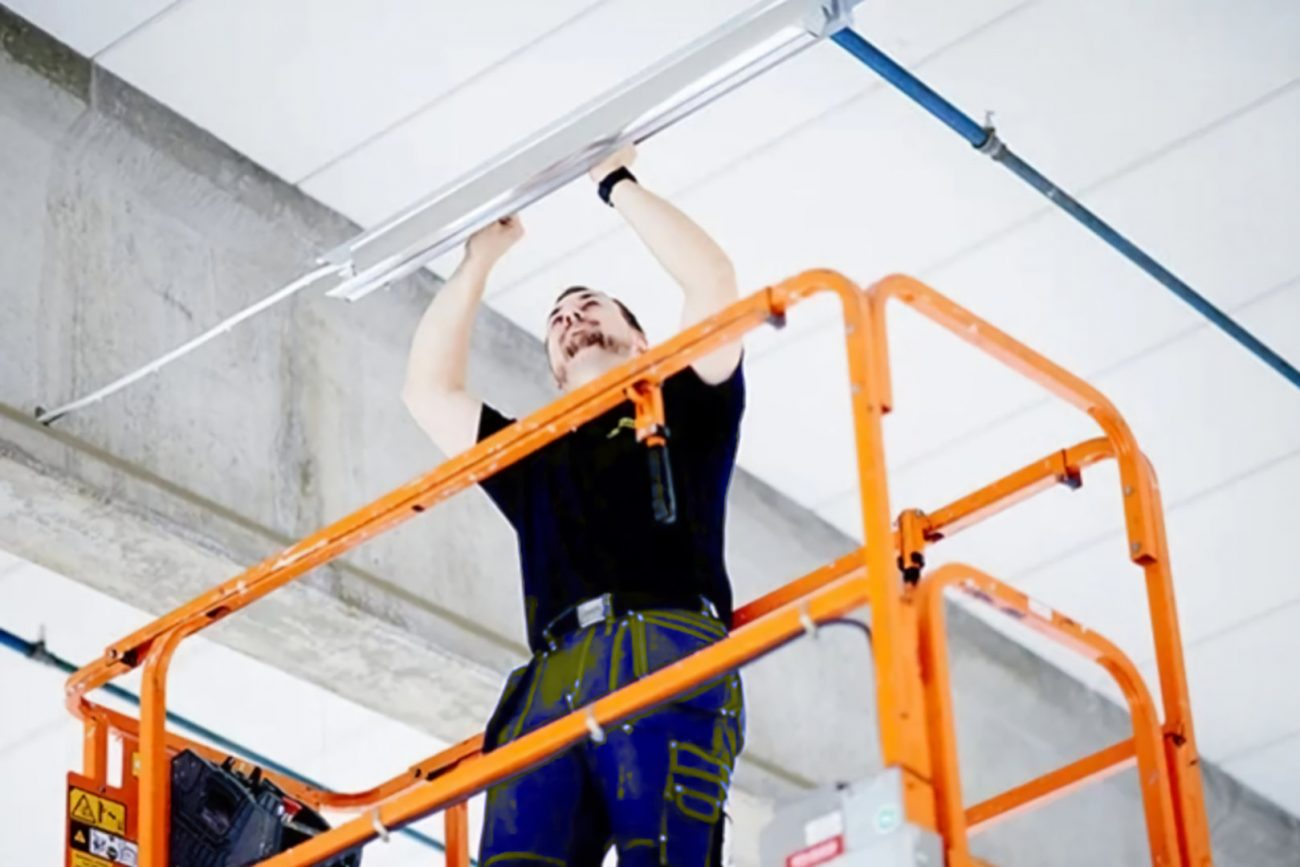 electrician using a scissor lift working on lights
