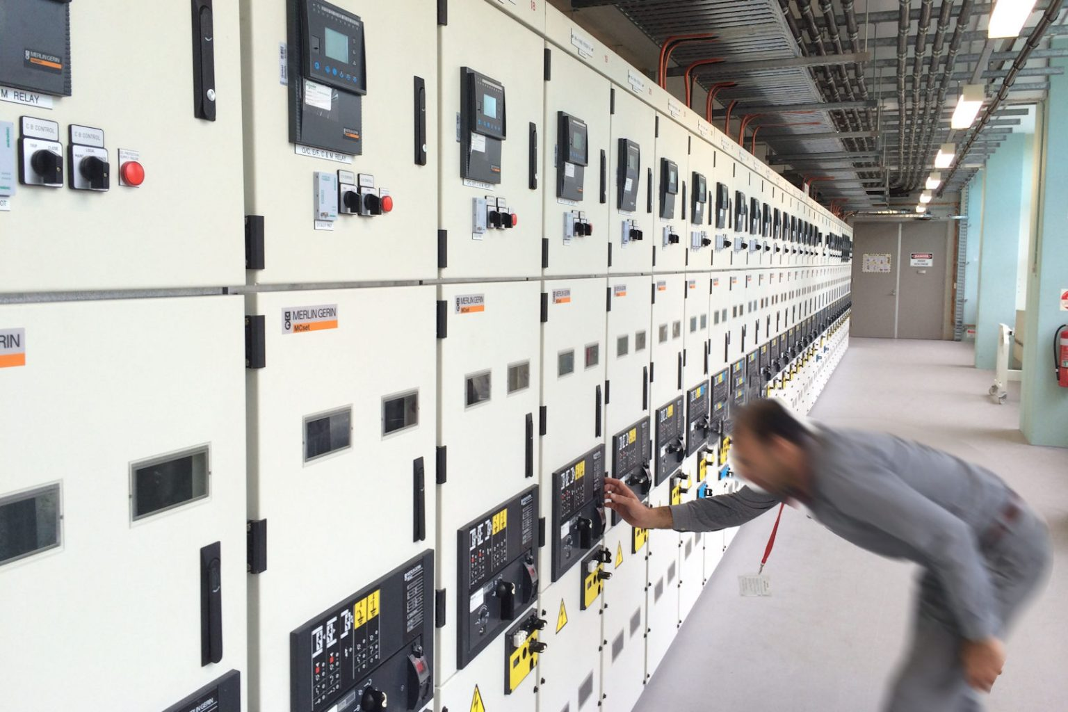 electrician switching circuit breaker on large main switchboard