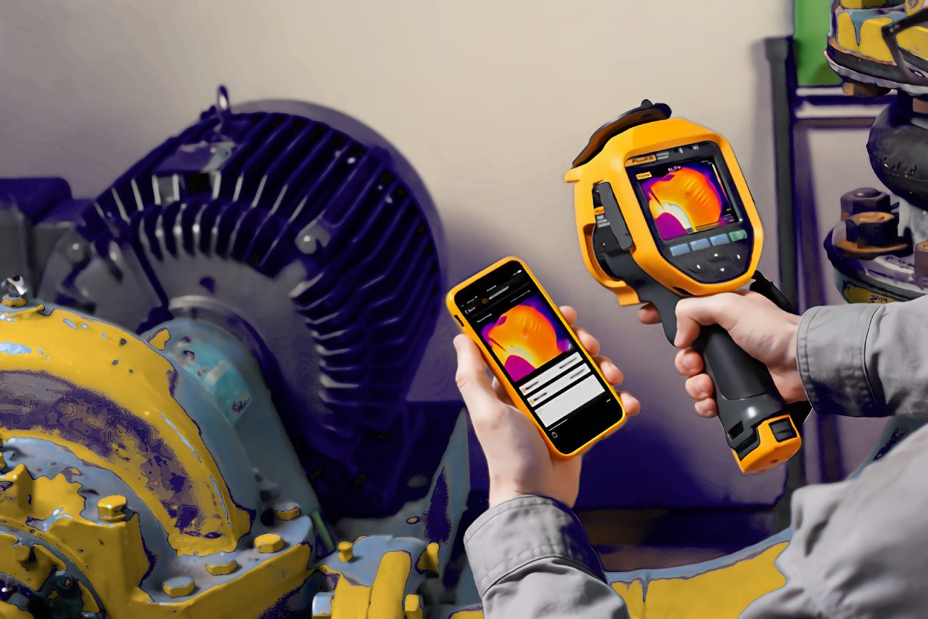 Technician thermal scanning HVAC electric motor using fluke thermal scanner and phone software